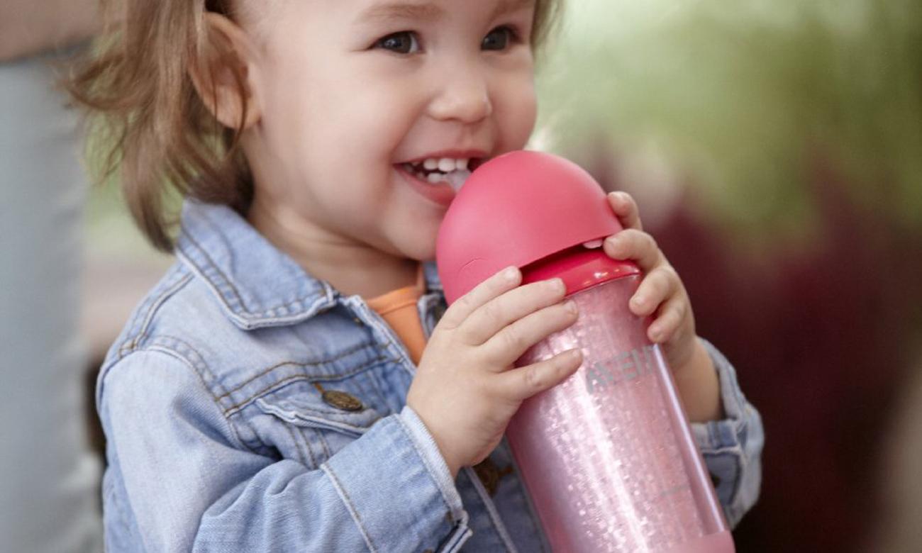 dziecko pije z użyciem kubek termiczny ze słomką różowy